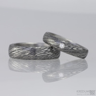 Ilustrační foto: Snubní prsteny damasteel, typ PRIMA + čirý diamant 2 mm. Struktura voda, lept 100% zatmavený, šířky 5,5 mm a 4,5 mm